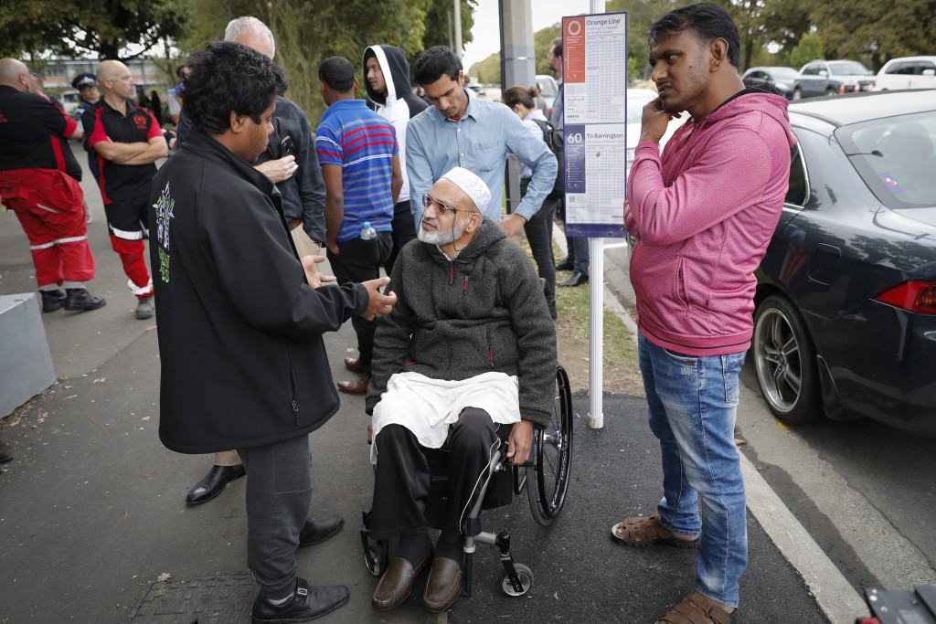 Farid Ahmed, center, a 59-year-old survivor of the Friday mosque attacks, talks with other relatives outside an information center for families, Satur