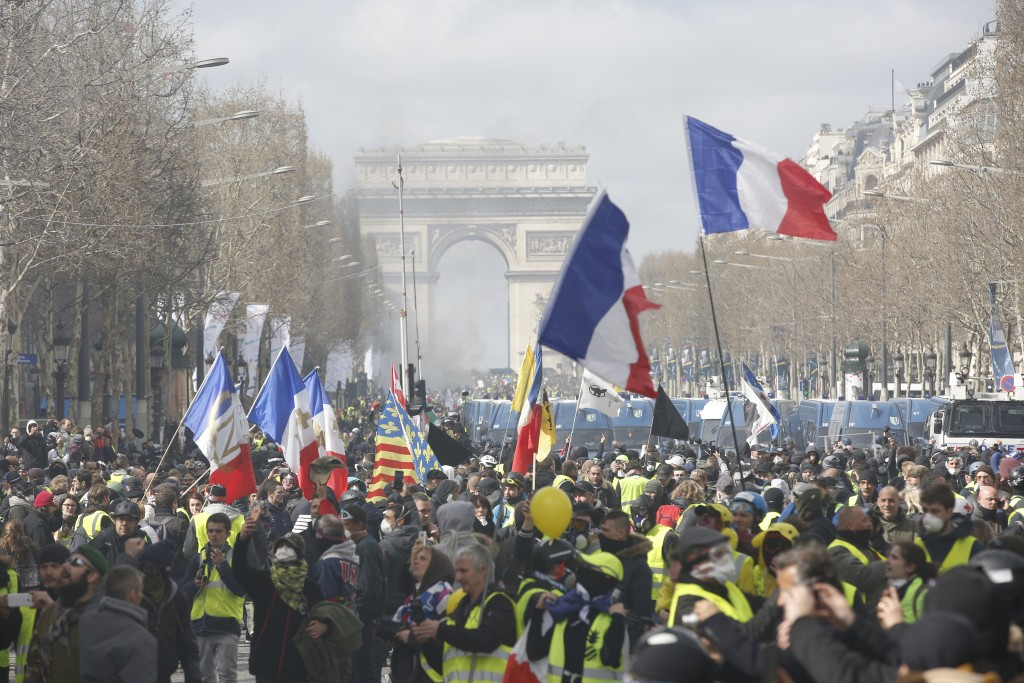 Yellow vests demonstrators invade the Champs Elysees avenue Saturday, March 16, 2019 in Paris. French yellow vest protesters clashed Saturday with rio