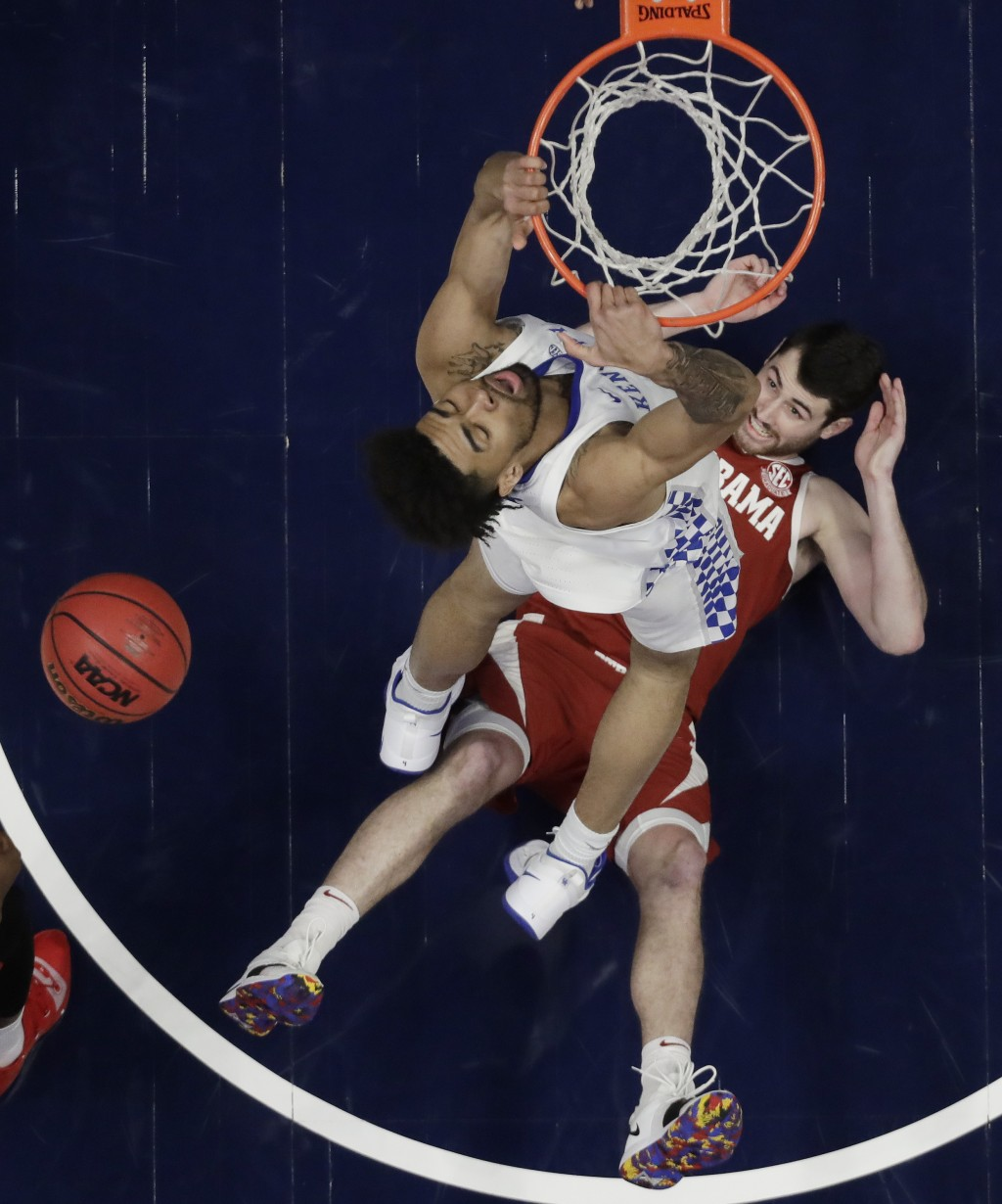 Alabama guard Riley Norris watches from the floor as Kentucky forward Nick Richards dunks the ball above him in the first half of an NCAA college bask