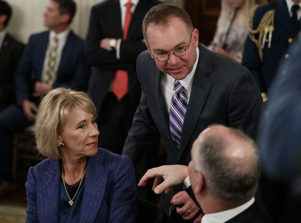 FILE - In this Feb. 25, 2019, file photo, Education Secretary Betsy DeVos, left, acting White House chief of staff Mick Mulvaney, center, and Louisian