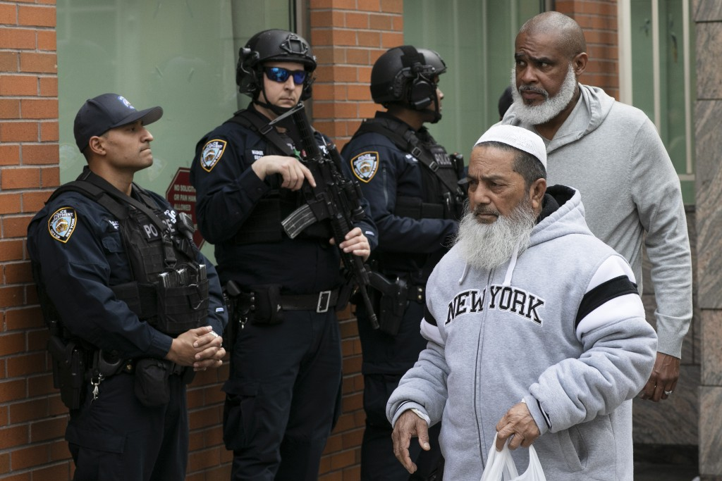 Men leave the Islamic Cultural Center of New York under increased police security following the shooting in New Zealand, Friday, March 15, 2019, in Ne
