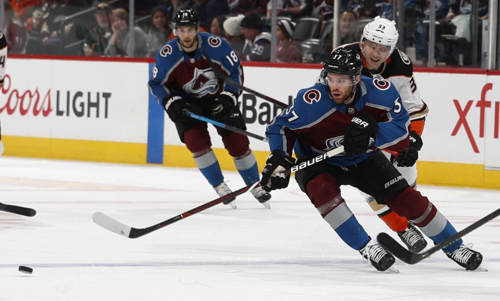 Colorado Avalanche left wing J.T. Compher, front, pursues the puck with Anaheim Ducks right wing Jakob Silfverberg during the first period of an NHL h...