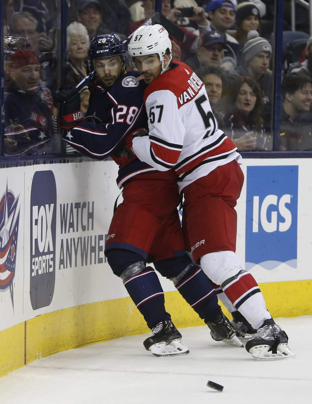 Carolina Hurricanes' Trevor van Riemsdyk, right, checks Columbus Blue Jackets' Oliver Bjorkstrand, of Denmark, away from the puck during the first per