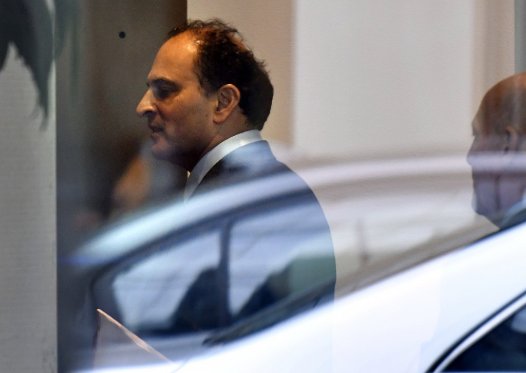 David Sidoo, of Vancouver, Canada, enters an adjacent building with his lawyer following a federal court hearing Friday, March 15, 2019, in Boston. Si