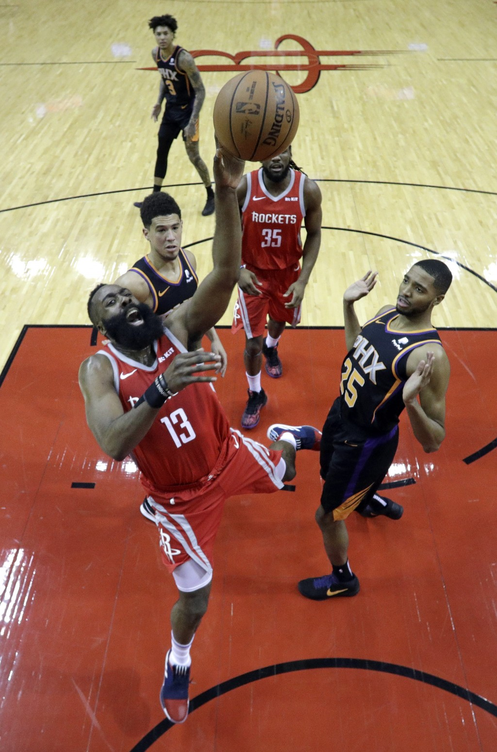 Houston Rockets' James Harden (13) shoots as Phoenix Suns' Mikal Bridges (25) and Devin Booker, left, defend during the first half of an NBA basketbal