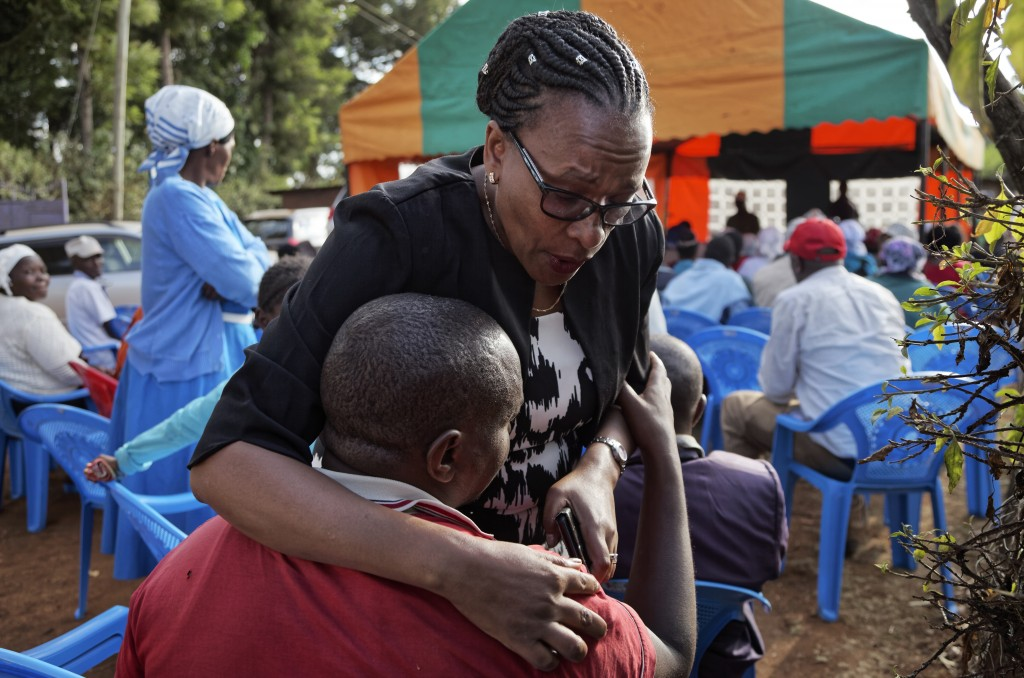 In this photo taken Thursday, March 14, 2019, sister Goreti Kimani consoles brother Chira Kageche at a memorial service for their brother, Catholic pr