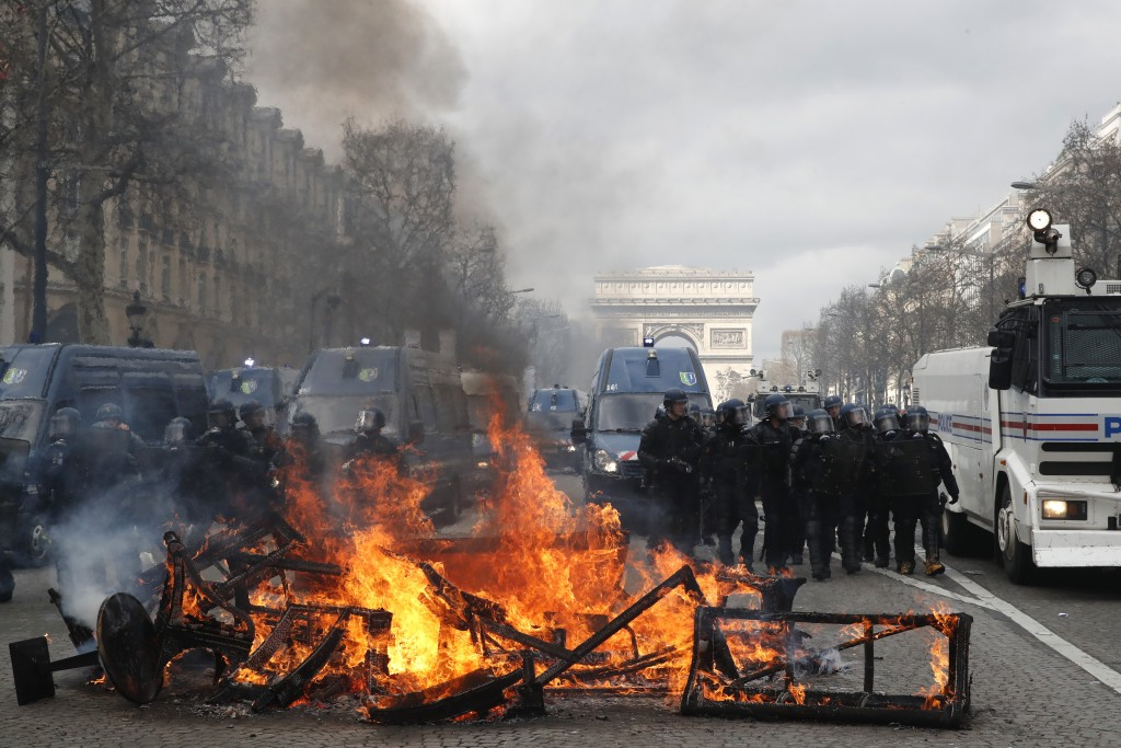 A barricade burns on the Champs Elysees avenue Saturday, March 16, 2019 in Paris. French yellow vest protesters clashed Saturday with riot police near