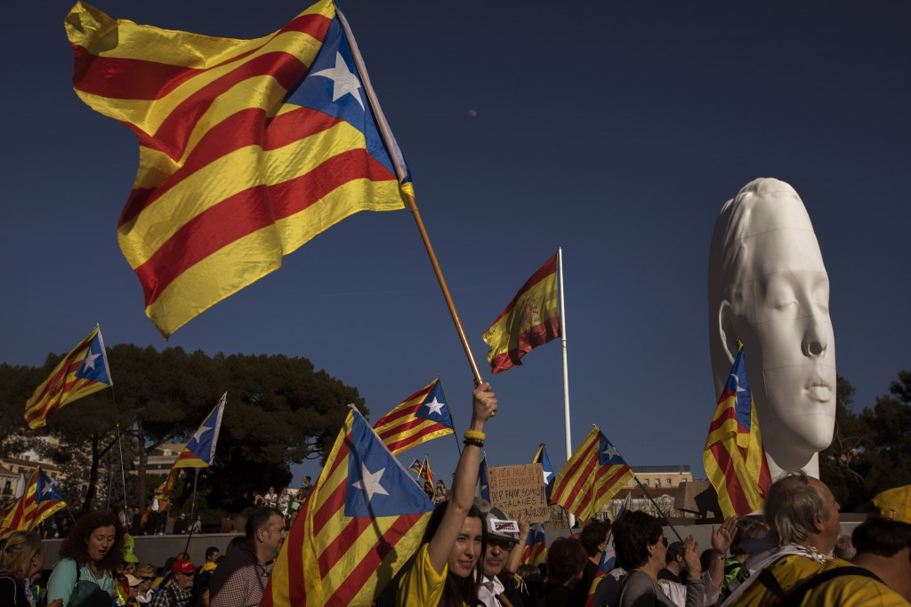 "Catalan pro-independence demonstrators hold ""estelada,"" or separatist flags, as they arrive to Madrid, Spain, Saturday, March 16, 2019. Demonstrators"