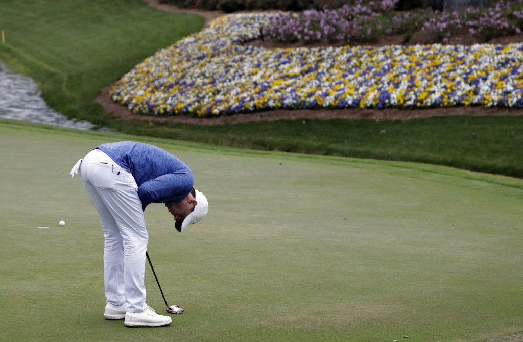 Rory McIlroy, of Northern Ireland, bends over after missing a birdie putt on the 13th green during the third round of The Players Championship golf to