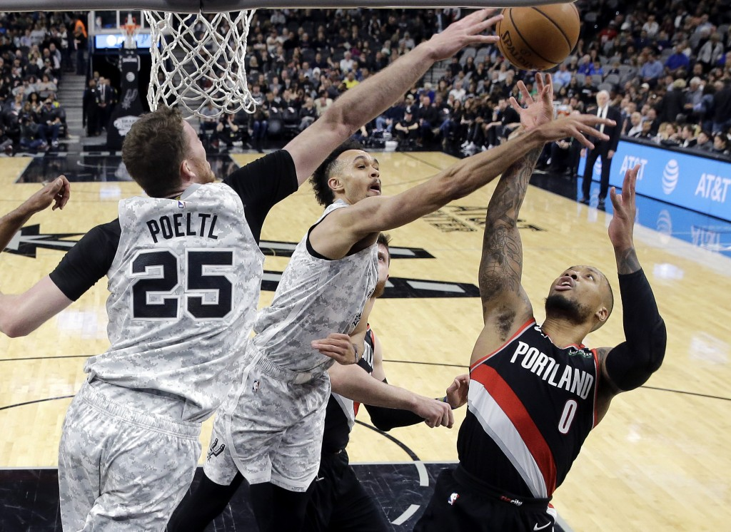 Portland Trail Blazers guard Damian Lillard (0) is blocked as he tries to score against San Antonio Spurs center Jakob Poeltl (25) and guard Derrick W