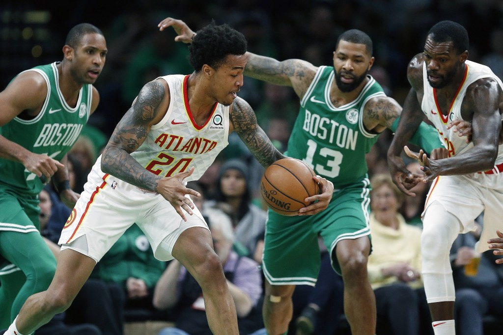 Atlanta Hawks' John Collins (20) retains control of the ball against Boston Celtics' Al Horford, left, and Marcus Morris (13) during the first half of