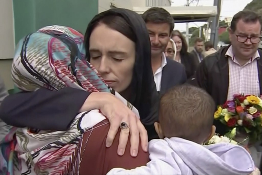 In this image made from video, New Zealand's Prime Minister Jacinda Ardern, center, hugs and consoles a woman as she visited Kilbirnie Mosque to lay f