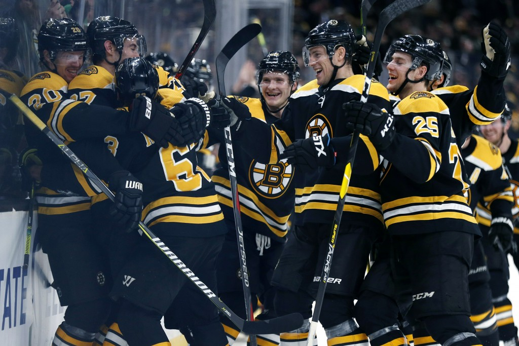 Boston Bruins celebrate after a goal by Brad Marchand (63) during overtime in an NHL hockey game against the Columbus Blue Jackets in Boston, Saturday
