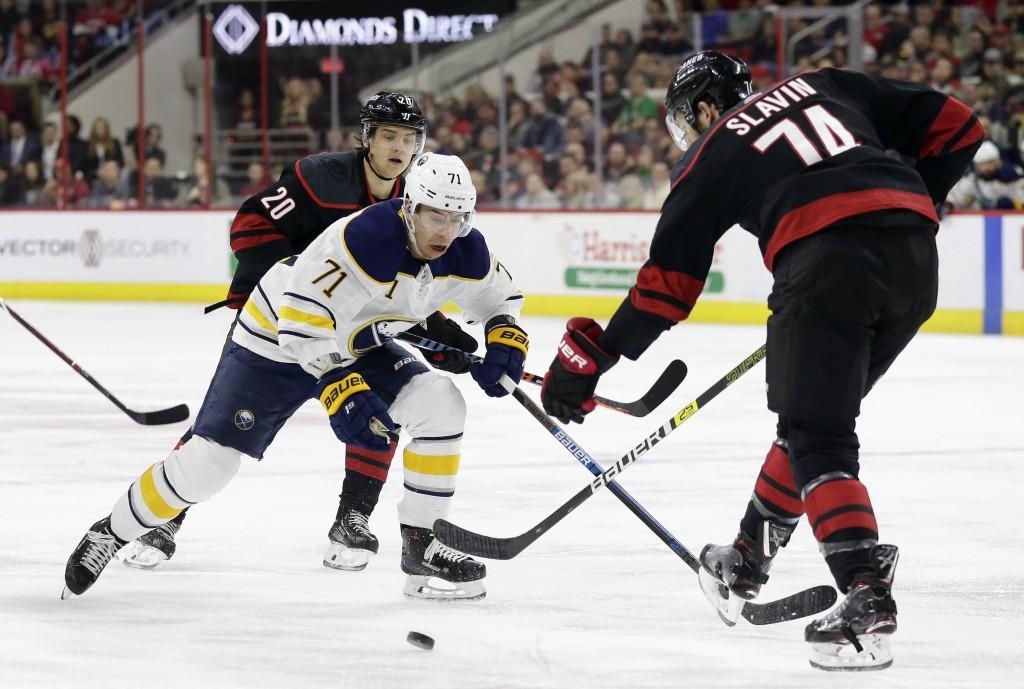 Buffalo Sabres' Evan Rodrigues (71) skates between Carolina Hurricanes' Sebastian Aho (20), of Finland, and Jaccob Slavin (74) during the first period
