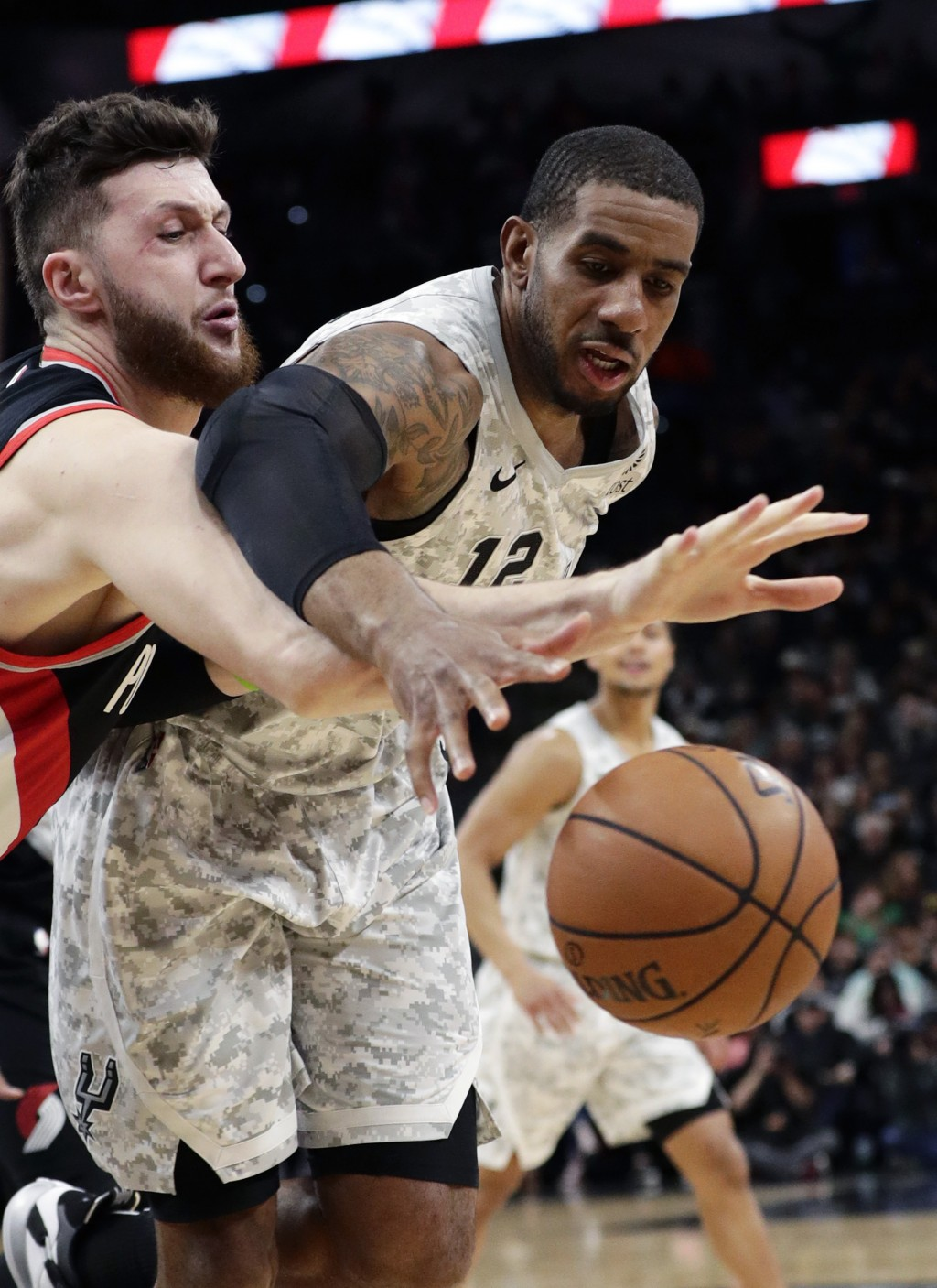 San Antonio Spurs center LaMarcus Aldridge (12) loses control of the ball as Portland Trail Blazers center Jusuf Nurkic, left, reaches in during the f