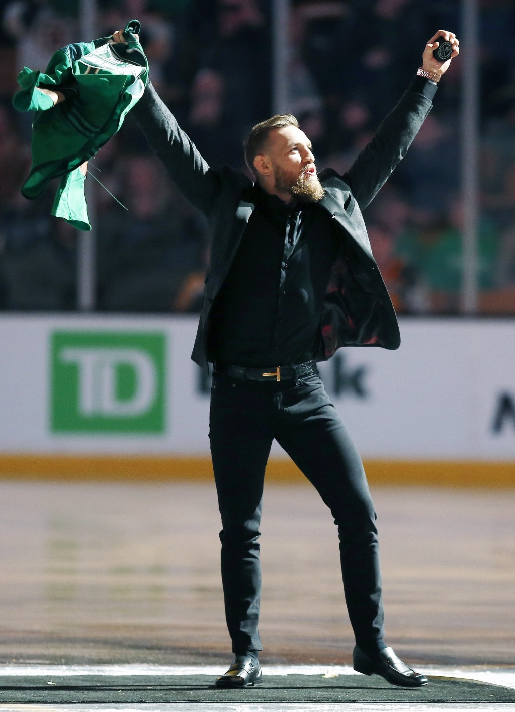 Mixed martial arts fighter and boxer Conor McGregor salutes the crowd before making the ceremonial puck drop at an NHL hockey game between the Boston