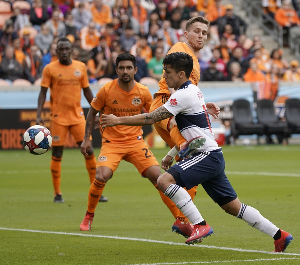 Vancouver Whitecaps's Fredy Montero, right, is fouled by Houston Dynamo's Adam Lundqvist inside the penalty box during the first half of an MLS soccer