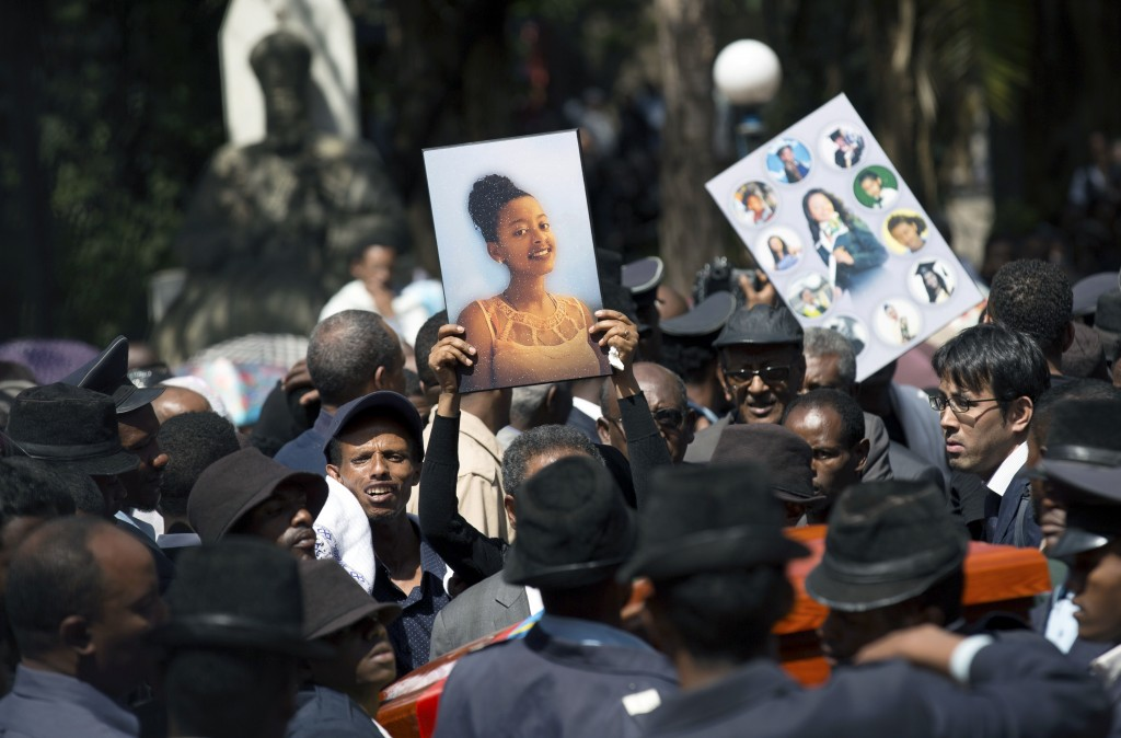 Relatives hold photographs of the victims at a mass funeral at the Holy Trinity Cathedral in Addis Ababa, Ethiopia Sunday, March 17, 2019. Thousands o