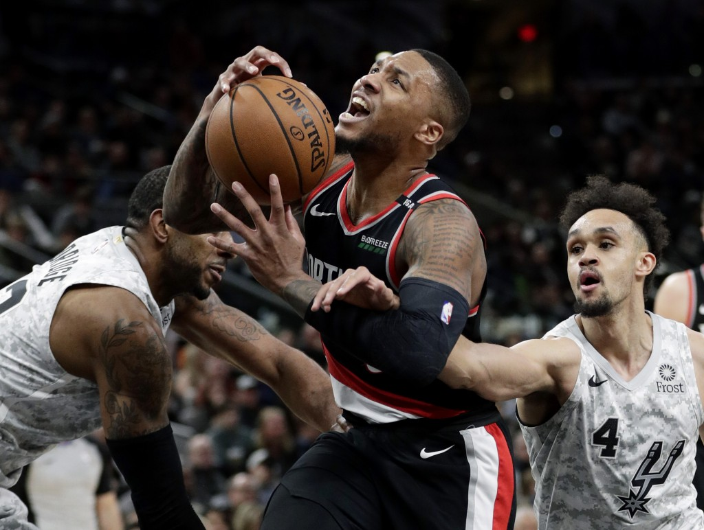 Portland Trail Blazers guard Damian Lillard (0) is fouled by San Antonio Spurs guard Derrick White (4) as he drives to the basket during the second ha