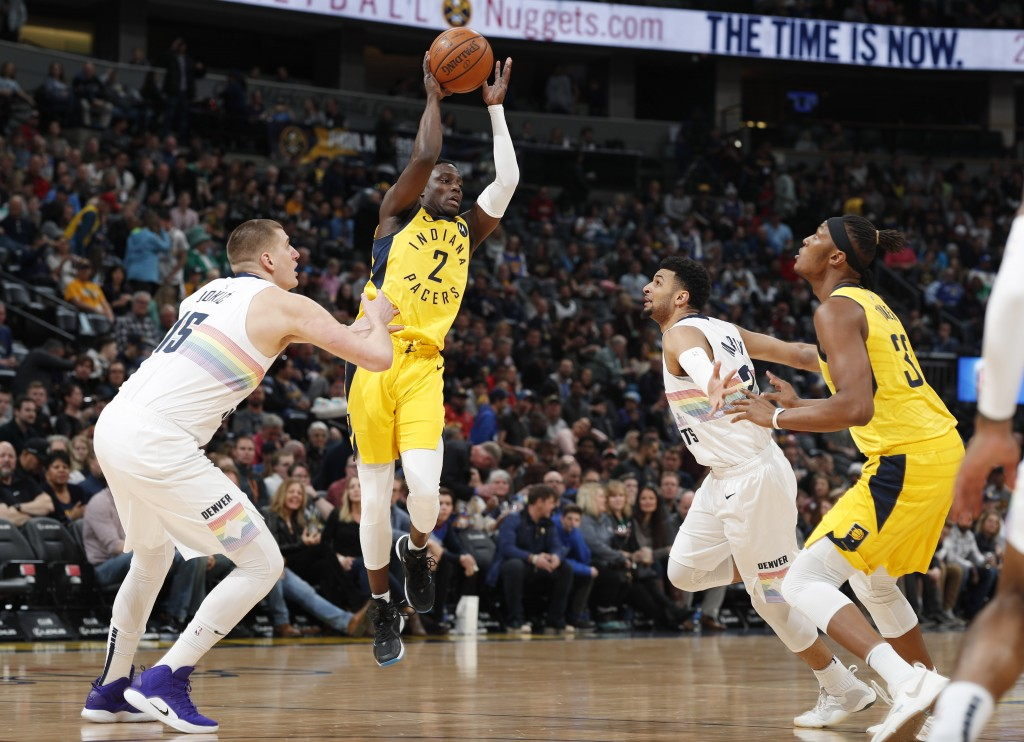Indiana Pacers guard Darren Collison, second from left, looks to pass the ball to center Myles Turner, right, as Denver Nuggets center Nikola Jokic, l