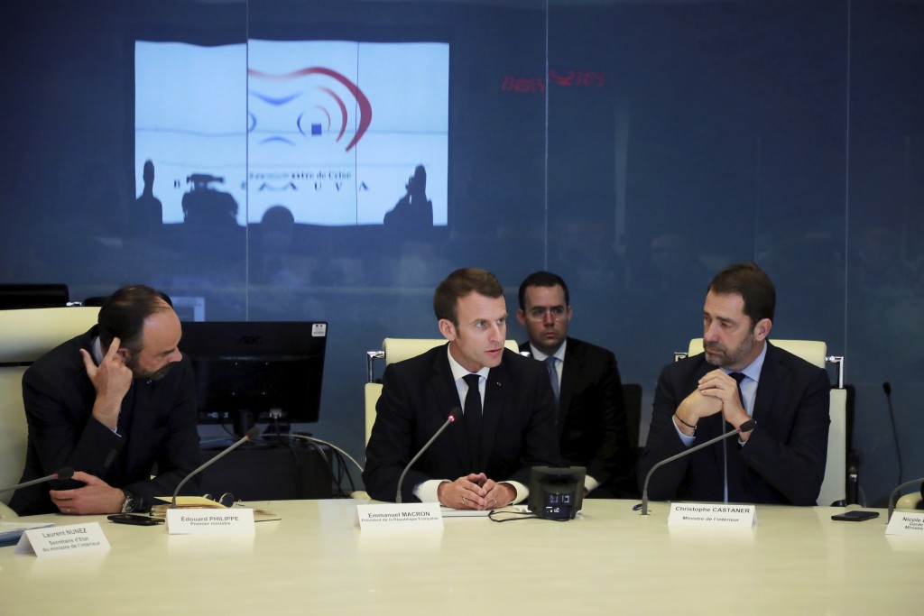 French President Emmanuel Macron, center, presides over an emergency crisis meeting with French Prime Minister Edouard Philippe, left, and French Inte
