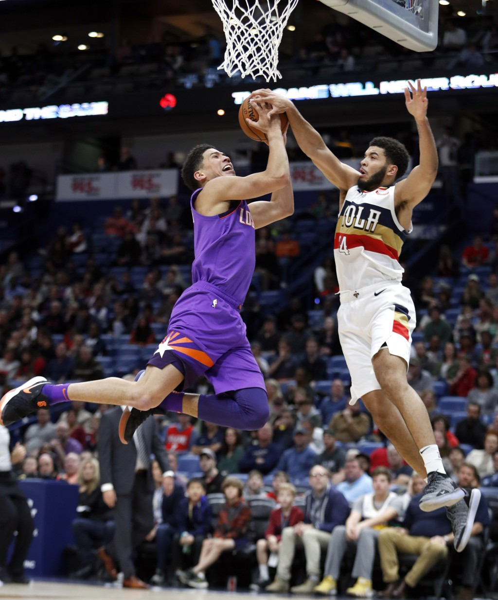 Phoenix Suns guard Devin Booker (1) is blocked by New Orleans Pelicans guard Kenrich Williams (34) during the first half of an NBA basketball game in