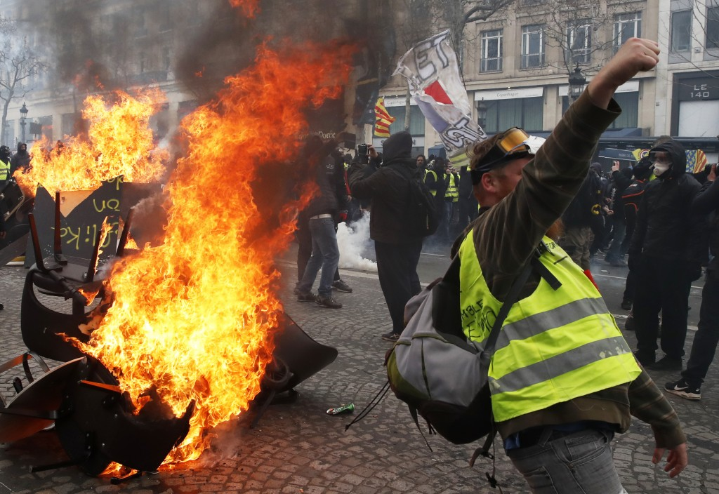 A protester shouts slogans in front of a barricade on fire during a yellow vests demonstration Saturday, March 16, 2019 in Paris. Paris police say mor