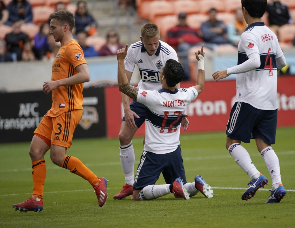 Vancouver Whitecaps's Fredy Montero (12) celebrates with Andy Rose, rear, after scoring on a penalty kick as Houston Dynamo's Adam Lundqvist (3) runs