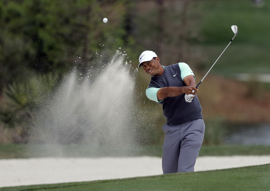 Tiger Woods blasts from a sand trap on the second hole during the third round of The Players Championship golf tournament Saturday, March 16, 2019, in