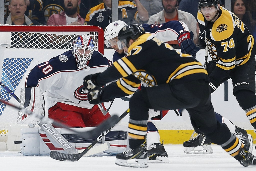 Boston Bruins' Patrice Bergeron, foreground, scores on Columbus Blue Jackets' Joonas Korpisalo (70) during the first period of an NHL hockey game in B
