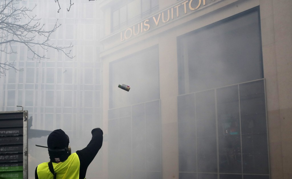 A protester throws a device on the Louis Vuitton luxury shop on the Champs Elysees avenue, during a yellow vests demonstration Saturday, March 16, 201