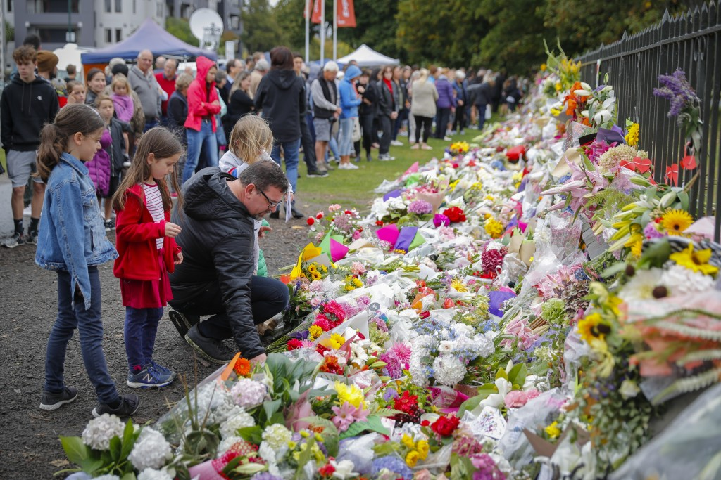 CORRECTS DATE- Mourners lay flowers on a wall at the Botanical Gardens in Christchurch, New Zealand, Sunday, March 17, 2019. New Zealand's stricken re