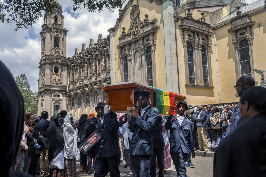 Relatives grieve next to empty caskets draped with the national flag at a mass funeral at the Holy Trinity Cathedral in Addis Ababa, Ethiopia Sunday,