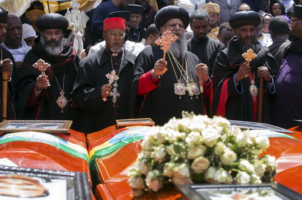 Church leaders pray next to empty caskets draped with the national flag at a mass funeral at the Holy Trinity Cathedral in Addis Ababa, Ethiopia Sunda