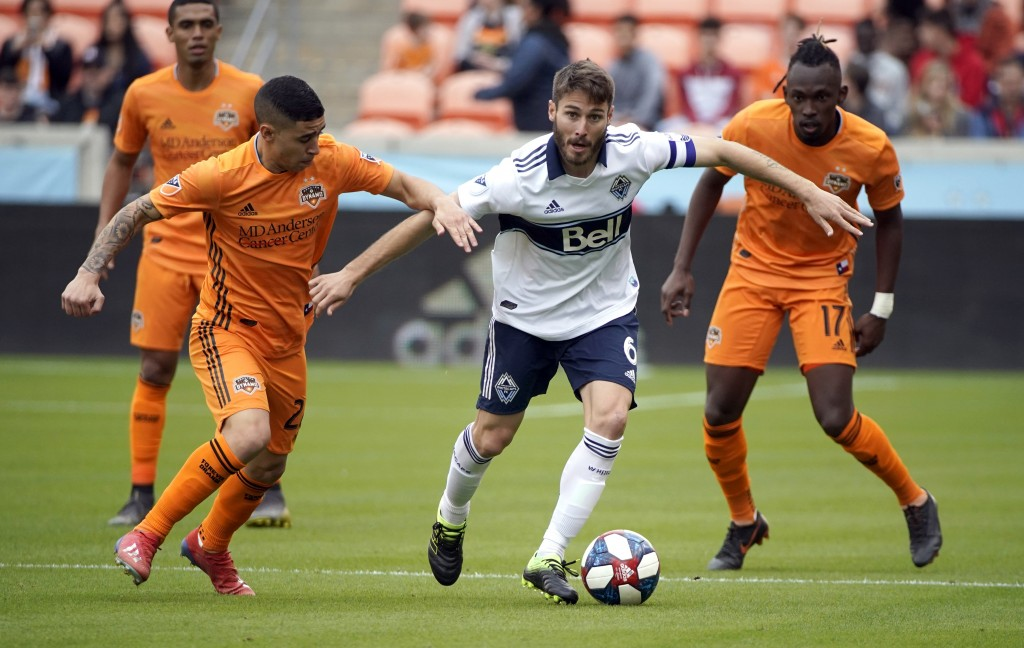 Houston Dynamo's Matias Vera (22) challenges Vancouver Whitecaps's Ion Erice (6) for the ball during the first half of an MLS soccer match Saturday, M