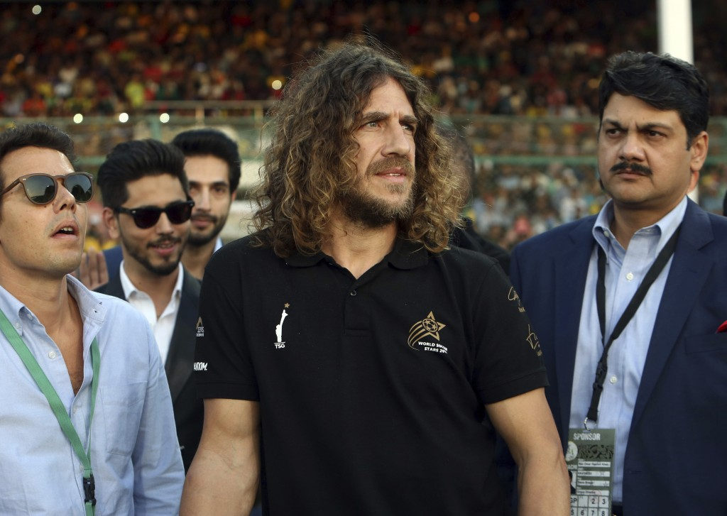 Retired Barcelona soccer player Carles Puyol, center, arrives to attend the closing ceremony of the Pakistan Super League, prior to the final cricket