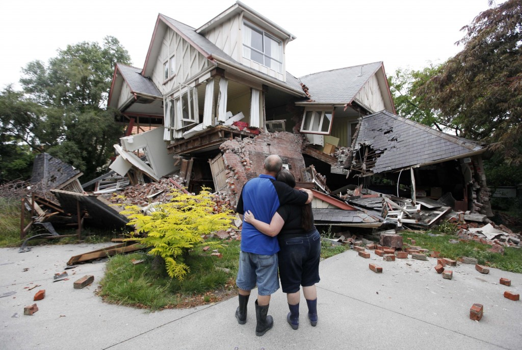 FILE - In this Feb. 23, 2011, file photo Murray, left, and Kelly James look at their destroyed house in central Christchurch, New Zealand, a day after
