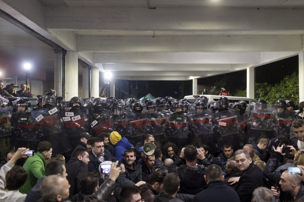 Protesters sit in front of a riot police cordon at an entrance to the state-run TV headquarters in Belgrade, Serbia, Saturday, March 16, 2019. Demonst