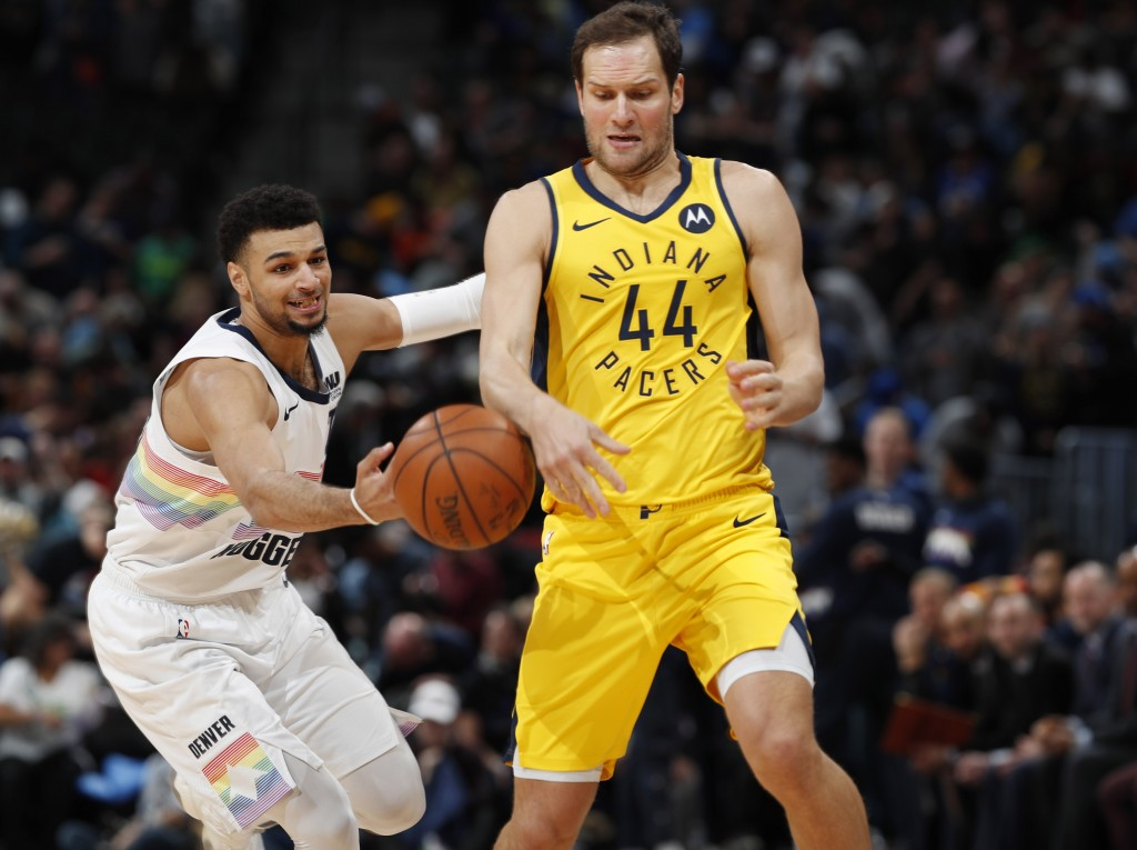 Denver Nuggets guard Jamal Murray, left, knocks the ball away from Indiana Pacers forward Bojan Bogdanovic during the first half of an NBA basketball