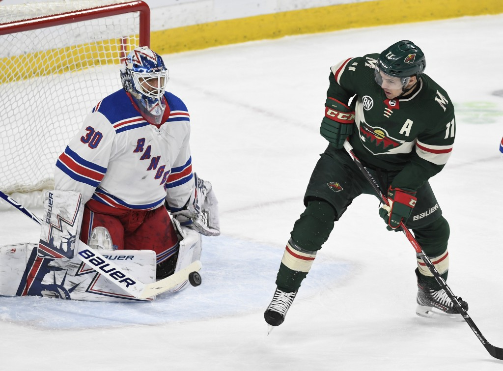 Minnesota Wild's Zach Parise, right, tips the puck past New York Rangers goalie Henrick Lundqvist, of Sweden, in the first period of an NHL hockey gam...