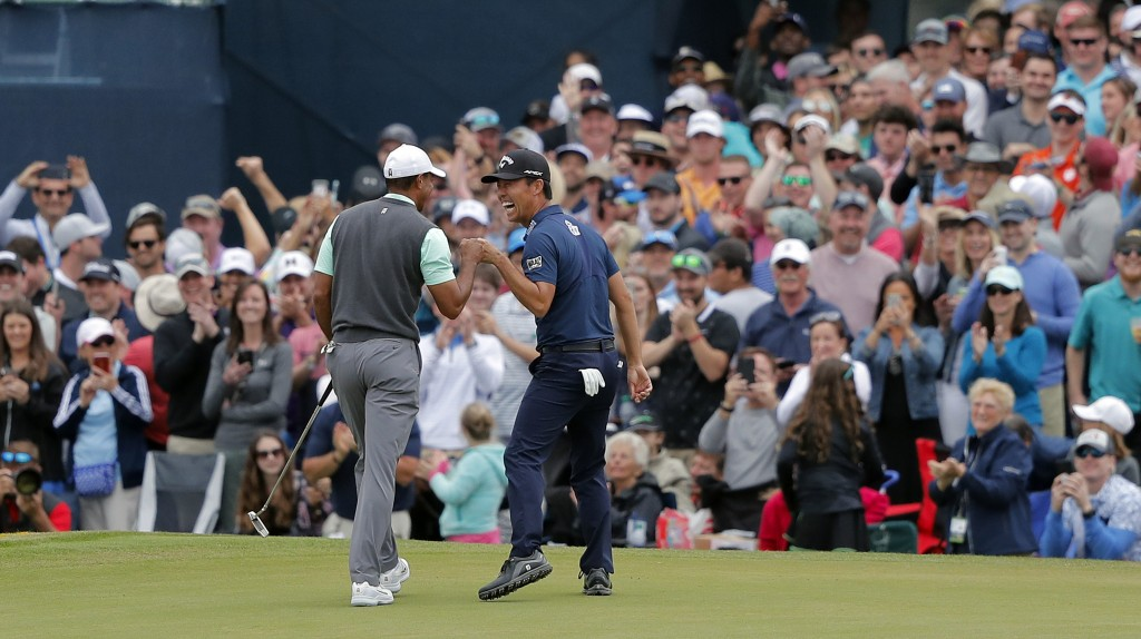 Tiger Woods, left, and Kevin Na share a laugh after putting out on the 17th green during the third round of The Players Championship golf tournament S...