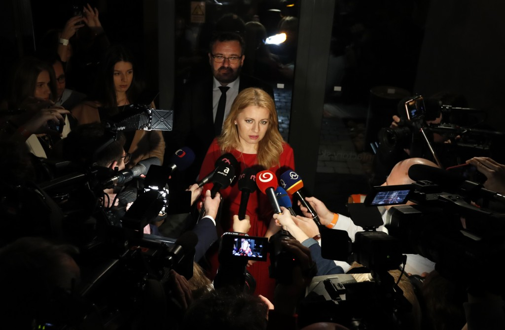 Presidential candidate Zuzana Caputova answers questions to media as she arrives at her election headquarters to watch the results of the first round