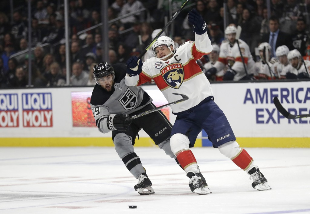 Florida Panthers' Aleksander Barkov, right, is defended by Los Angeles Kings' Alex Iafallo during the first period of an NHL hockey game Saturday, Mar