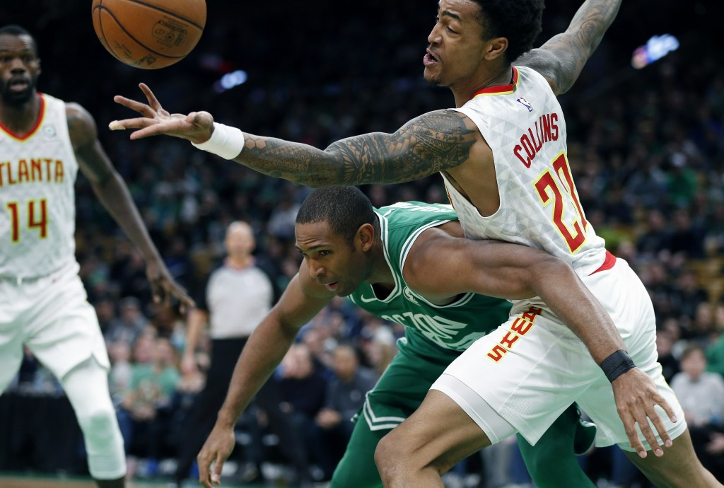 Atlanta Hawks' John Collins (20) and Boston Celtics' Al Horford battle for a loose ball during the first half of an NBA basketball game in Boston, Sat