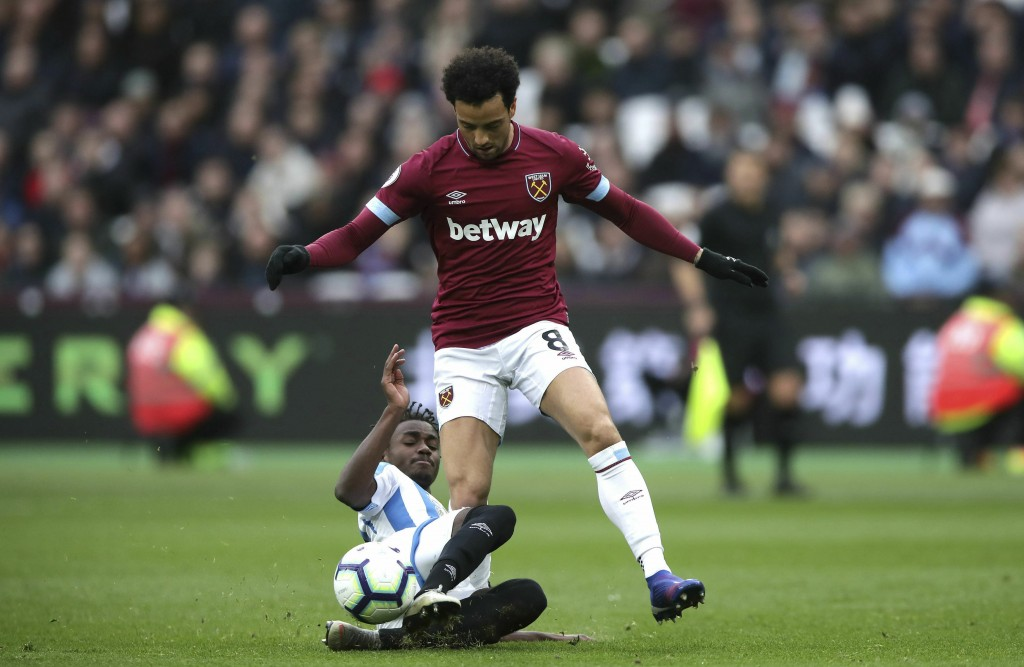 Huddersfield Town's Aaron Rowe, left, and West Ham United's Felipe Anderson battle for the ball during the English Premier League soccer match between