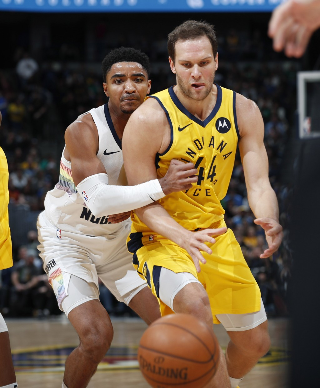 Indiana Pacers forward Bojan Bogdanovic, front, and Denver Nuggets guard Gary Harris watch the ball get away during the first half of an NBA basketbal
