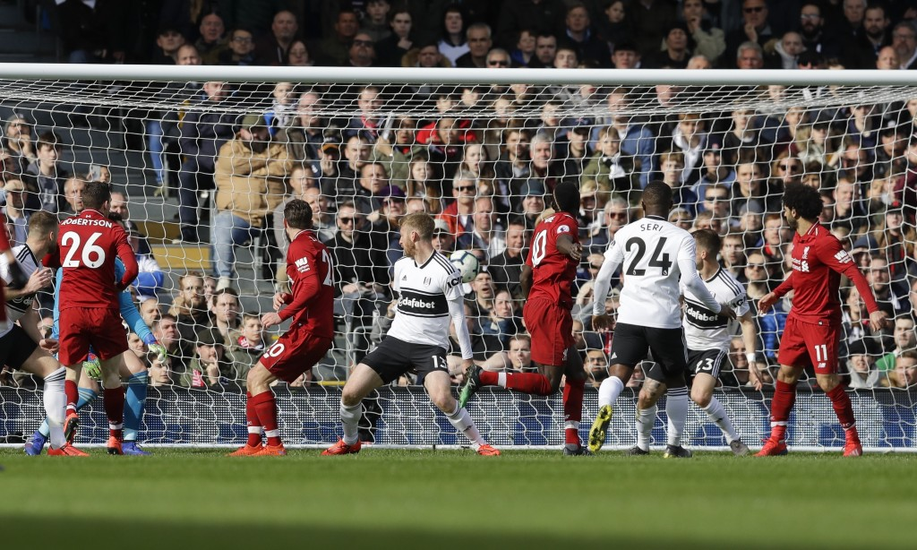 Liverpool's Sadio Mane, 4th from right, scores his side's opening goal during the English Premier League soccer match between Fulham and Liverpool at