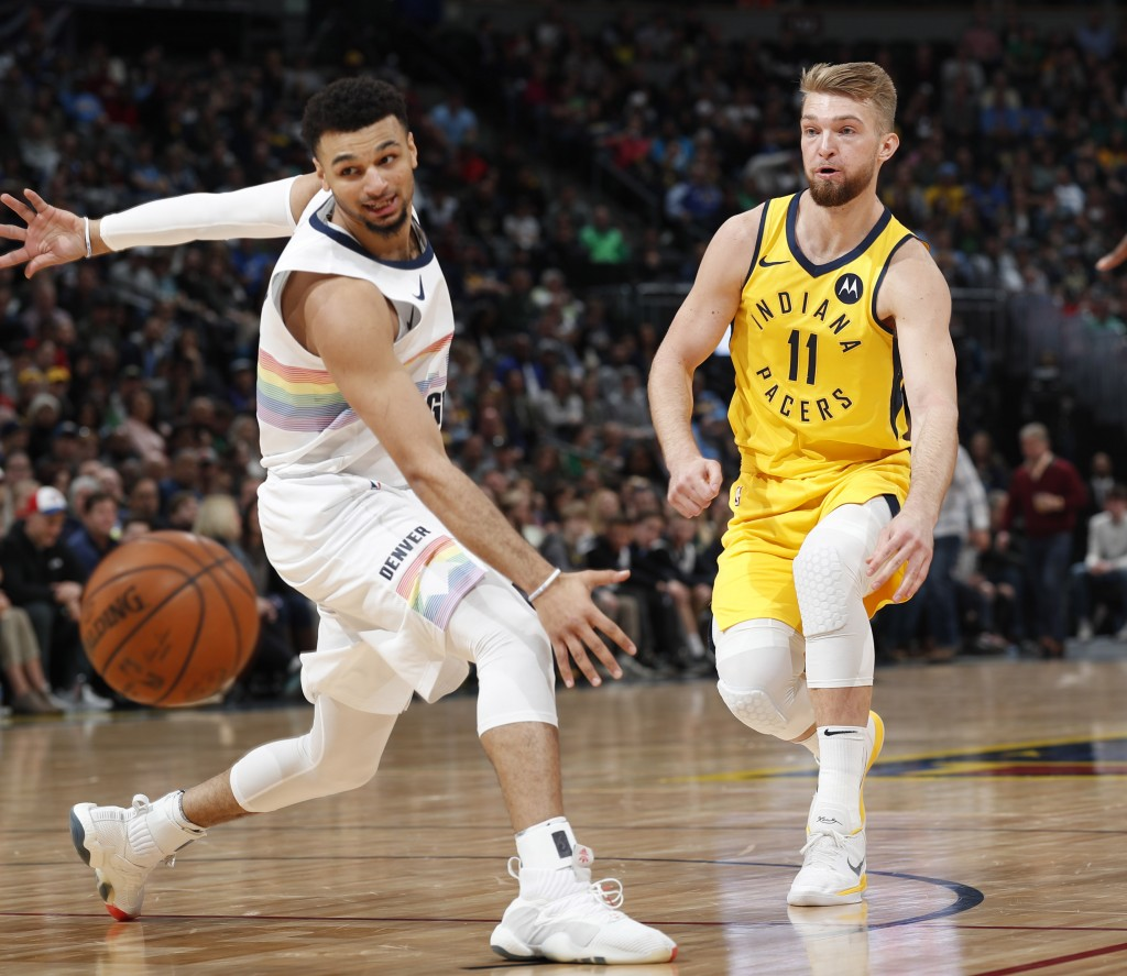 Indiana Pacers forward Domantas Sabonis, right, bounces a pass past Denver Nuggets guard Jamal Murray during the first half of an NBA basketball game