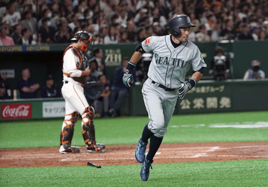 Seattle Mariners' Ichiro Suzuki flies out to center as Yomiuri Giants catcher Seiji Kobayashi stands at home in the second inning of their pre-season