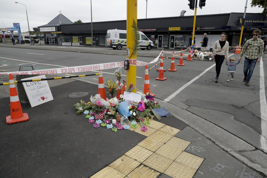 A family pays their respects at a makeshift memorial near the Linwood mosque in Christchurch, New Zealand, Sunday, March 17, 2019, where one of the tw
